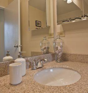 Center City apartment bathroom with storage vanity and granite top
