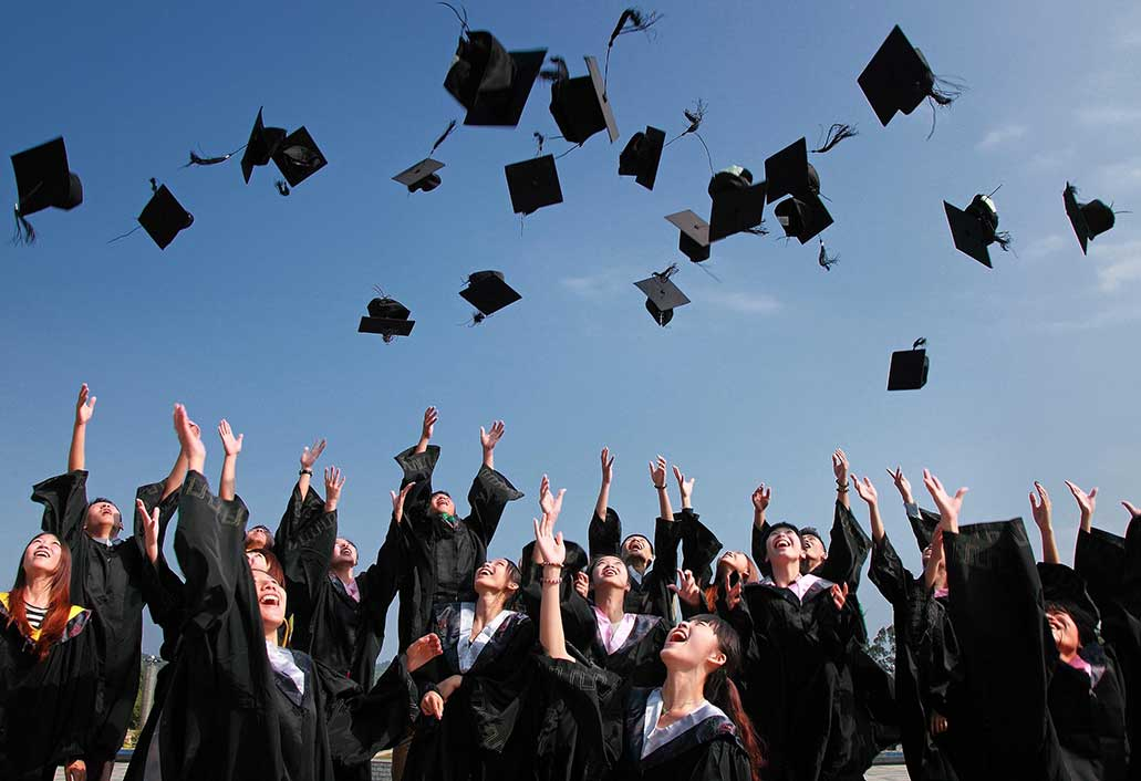 Group of college students tossing their caps in the air celebrating graduation